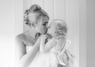 bride kissing baby daughter on her wedding day