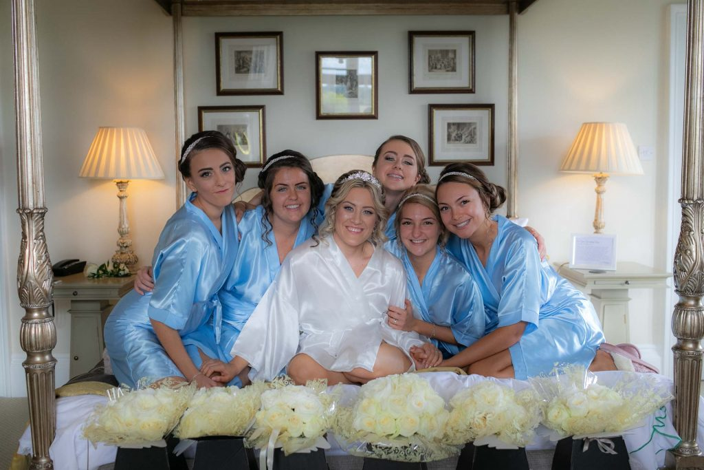 Bridesmaids together posing on a bed