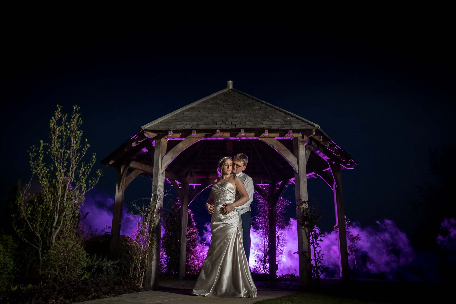 Evening photo of bride and groom with purple lighting